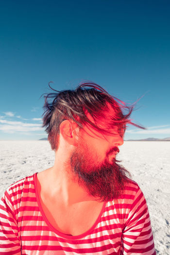 Mid adult man at beach against sky