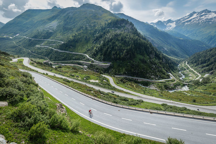 Aerial view of man riding bicycle on road amidst mountains against sky