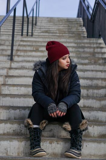 Without Reason One Person Sitting Staircase Clothing Architecture Winter International Women's Day 2019 Warm Clothing Full Length Hat Lifestyles Young Women Steps And Staircases Women Front View Adult Casual Clothing Real People Outdoors International Women's Day 2019 International Women's Day 2019