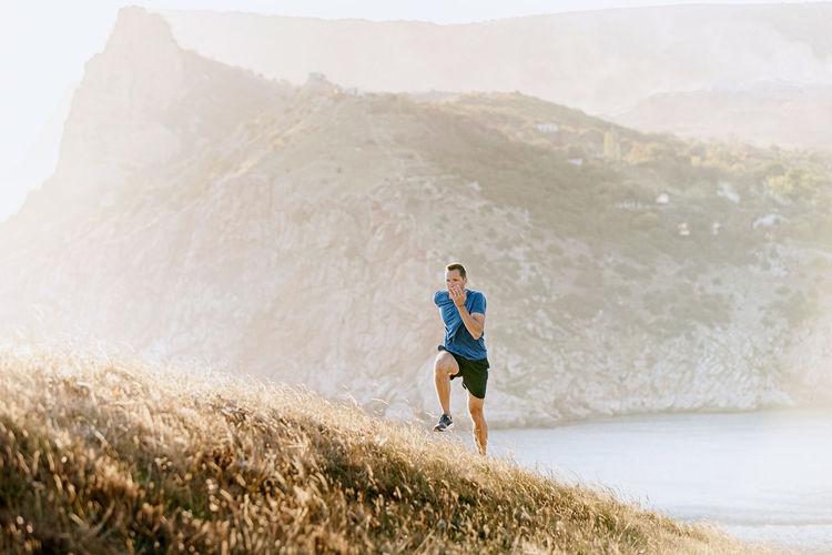 Male runner running uphill in sunset sea bay