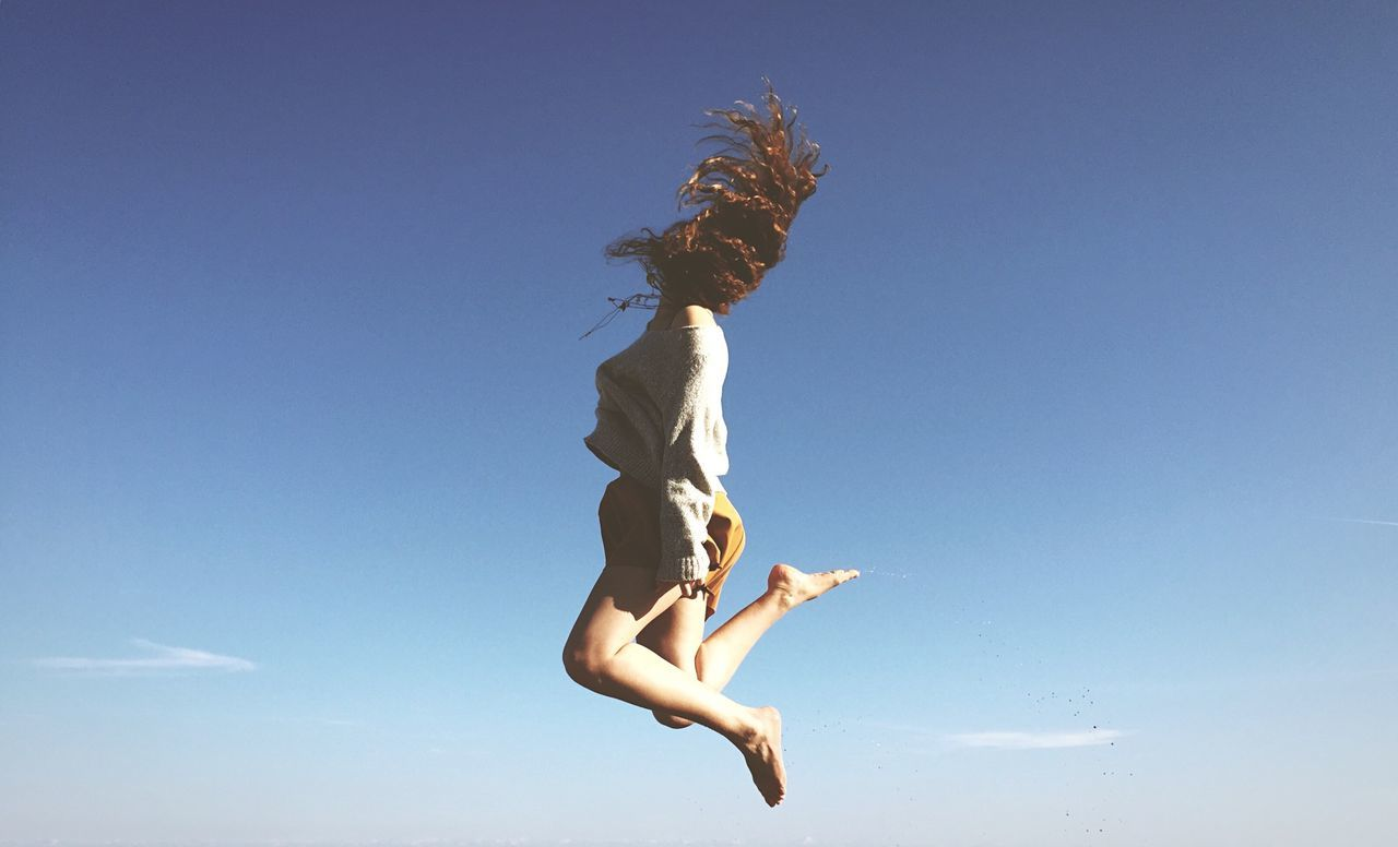 Full length of young woman tossing hair in mid-air against clear blue sky