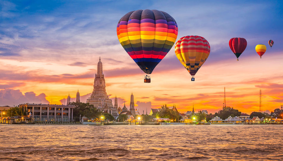 Colorful hot air balloons flying over Chao Phraya River near Wat Arun Temple at twilight in Bangkok, Thailand Arun Bangkok Chao Phraya River In Bangkok, Thailand Famous Pagoda Skyline Thailand Twilight Wat Arun (Temple Of Dawn) Adventure adventures in the city Balloon Flying Hot Air Balloon Landmark No People Outdoor Outdoors Real People Sky Sunset Tourism Tower Transportation Vacation