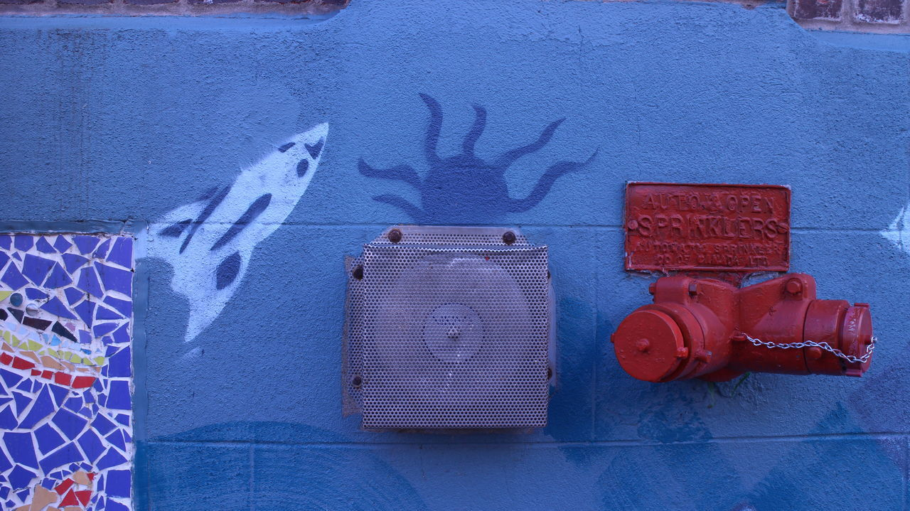 CLOSE-UP OF RED FIRE HYDRANT AGAINST WALL