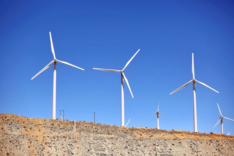 JGLowe EyeEm Selects Sky Blue Clear Sky Turbine Fuel And Power Generation Wind Turbine Wind Power Nature Low Angle View Renewable Energy Technology Alternative Energy Environmental Conservation Day Environment No People Sunlight Electricity  Built Structure