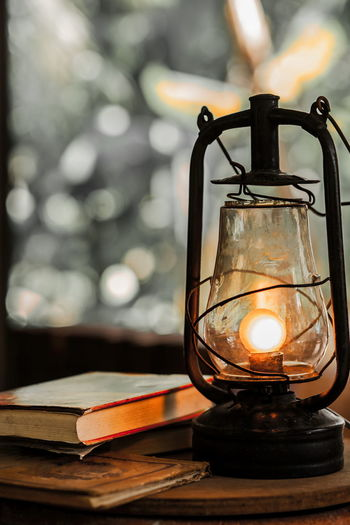 Close-Up Of Illuminated Lantern By Books On Table