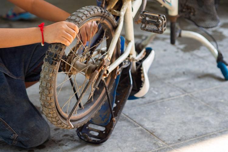 Kid boy repairing his bicycle
