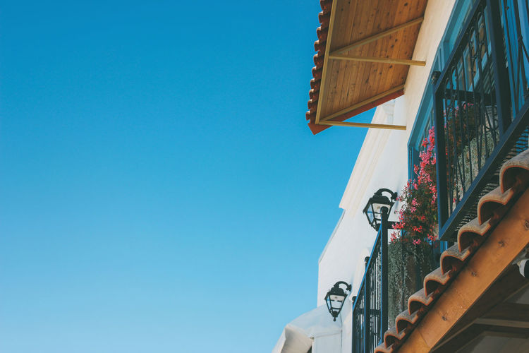 Beautiful roof facade of european cafe on the blue sky background, copy space
