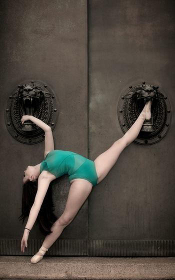 Ballet dancer dancing against wall