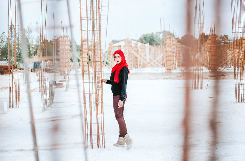 Portrait Of Beautiful Young Woman Standing At Construction Site During Winter