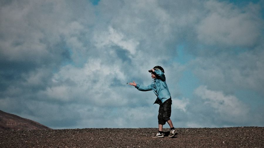 Woman jumping in park against cloudy sky