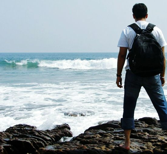 Sea Only Men Beach Standing Full Length Horizon Over Water Rock - Object Outdoors Men Lifestyles Leisure Activity One Person Sky Water Alone Standing Challenge Bag Denim Jeans White Simple Long Goodbye