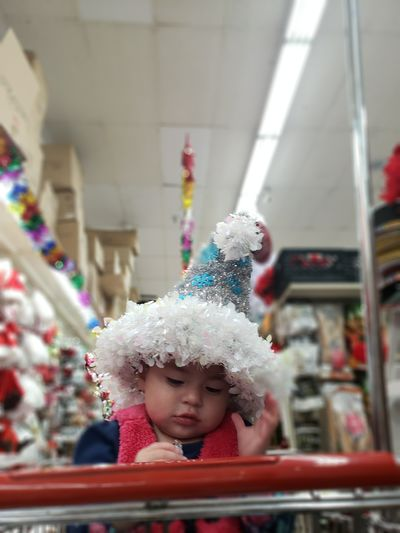 Baby girl wearing party hat while sitting on shopping cart in supermarket