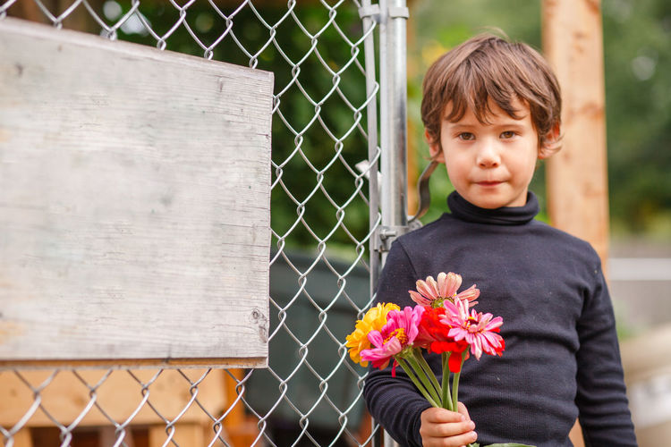 Portrait of boy standing by fence