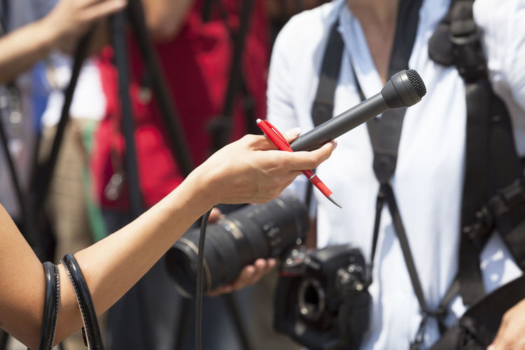 Cropped Hand Of Journalist Holding Microphone And Pen