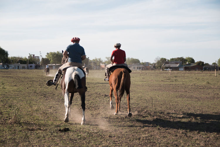 Argentinian father and son riding horse