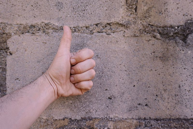 Close-up of hand gesturing thumbs up against wall outdoors