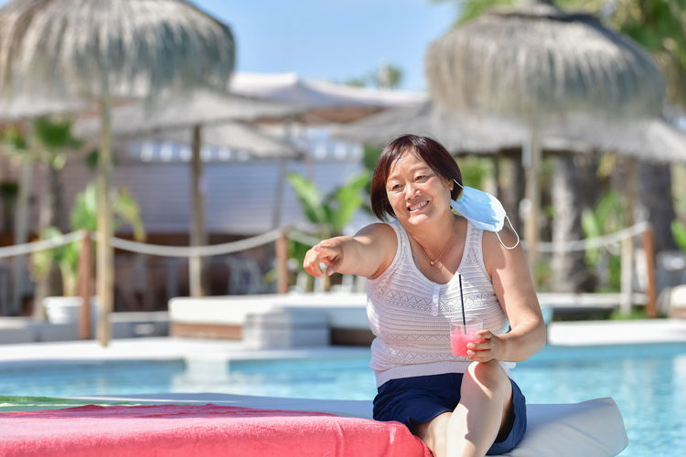 Full length of smiling young woman swimming pool