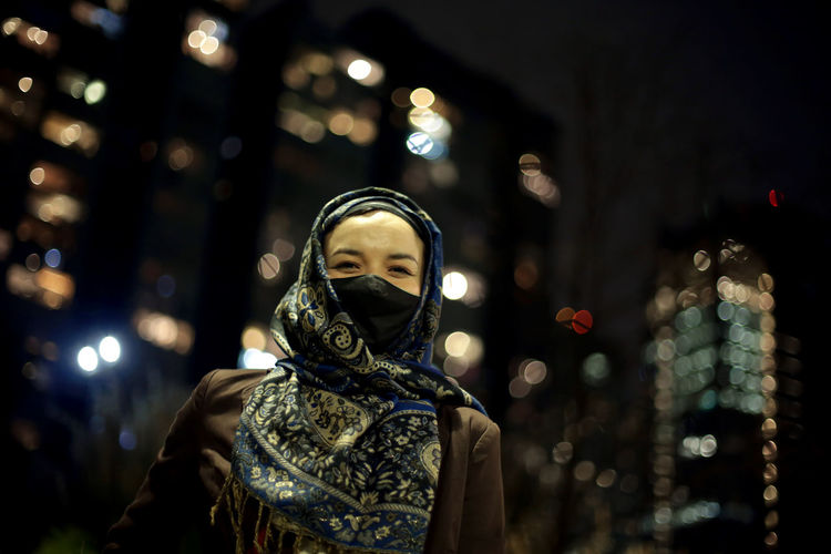 Low angle view of woman wearing hijab against city lights