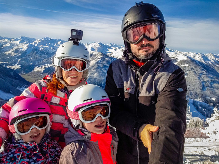 Smiling family standing against sky against mountain during winter