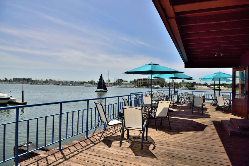 Sailing Embarcadero Cove 1 Jack London Square Oakland, Ca. Outdoor Cafe Observation Deck The Color Of Sport Sailboat Sailing Calm Waters Alameda Marina Waterfront Boat Launches Wet Berths Moored Sailboats Nautical Vessels Umbrellas Chairs Tables Shadows Handrails Too Early For Customers Roof Glass & Wood Door Horizon Over Water Tranquility Buildings