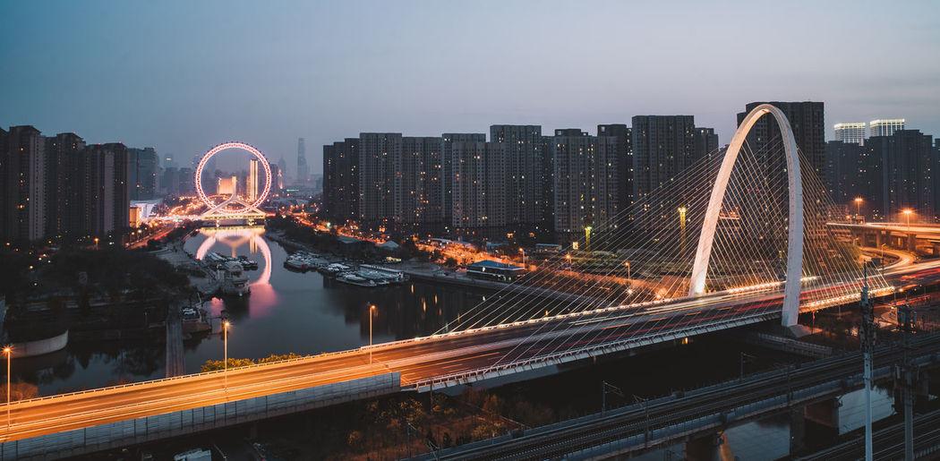 Illuminated bridge over river amidst buildings in city against sky