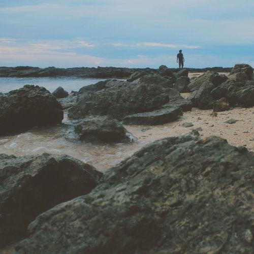 Man standing on rock at seaside