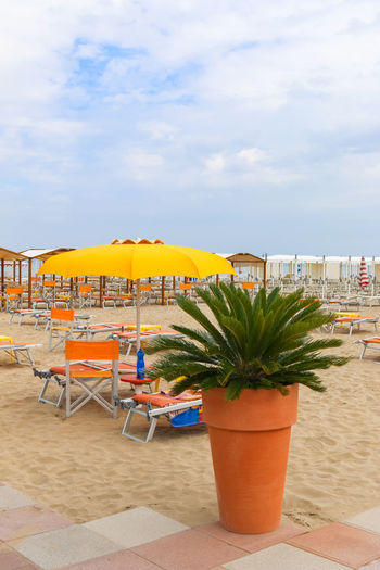 Empty beach, Italy, Riccione Italy. Riccione Rimini Vacations Beach Chair Cloud - Sky Day Emiliaromagna Italy No People Orange Color Outdoors Plant Potted Plant Resort Riccione Sand Sky Umbrella Chair Table Vacations Trip