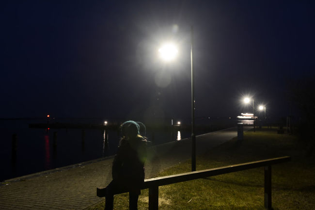 girl sitting on bench Baltic Sea Grief Lantern Lonely Neuendorf Silhouette Defocused Depressed Evening Girl Hiddensee Illuminated Mobbing Night One Person Outdoors Port Problem Shadow Spooky Street Light Teenager