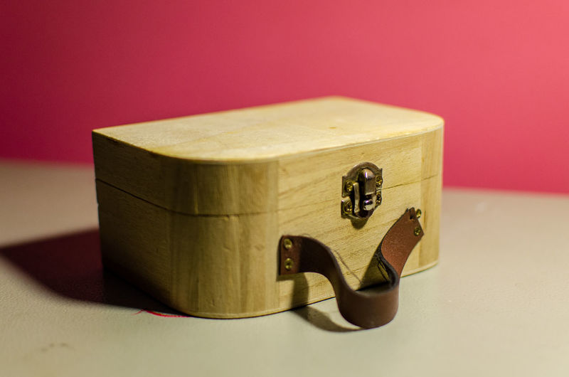 Close-up of wooden container on table against pink background