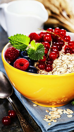 Raspberries With Red Currants And Breakfast Cereals In Bowl On Table