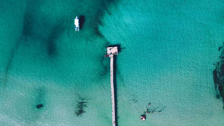 High angle view of blue sea against green wall