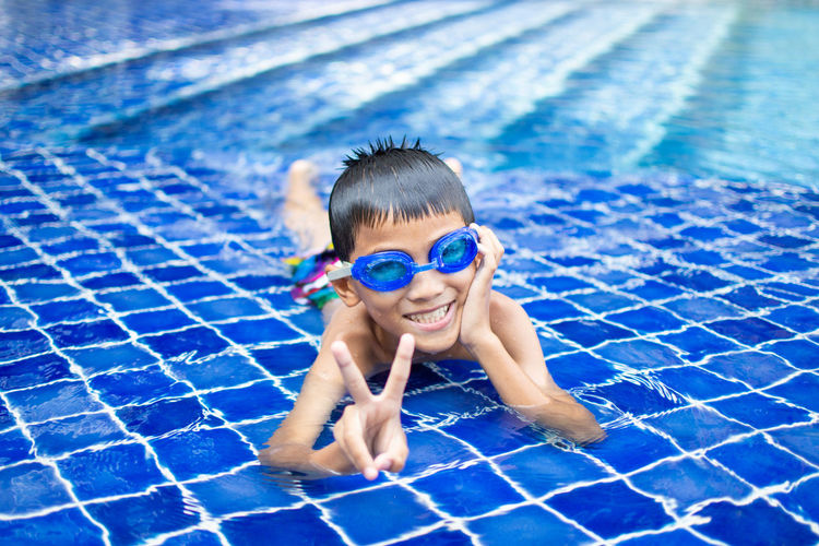 Pool Swimming Pool Child Water Swimming Childhood Happiness Smiling Swimwear Portrait Offspring Swimming Goggles Nature Looking At Camera Eyewear Front View Cheerful People Outdoors Positive Emotion
