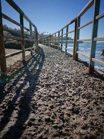 Shadow of railing on beach against sky