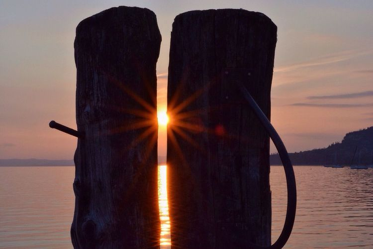 Wooden posts against lake garda during sunset