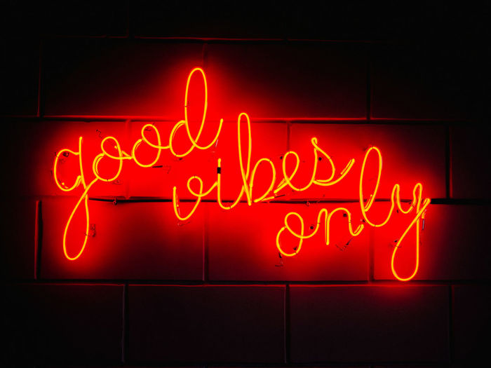 Illuminated text on red wall at night
