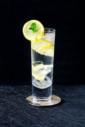 Glass of drink on table against black background