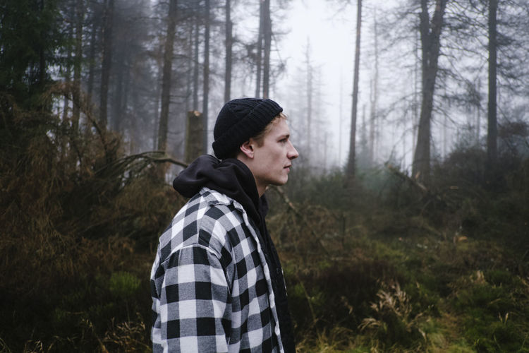 Side view of man looking way while standing in forest