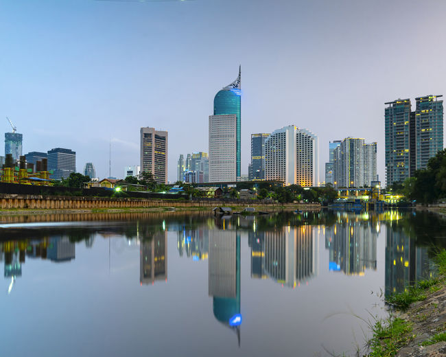 Reflection of buildings in lake against sky in city