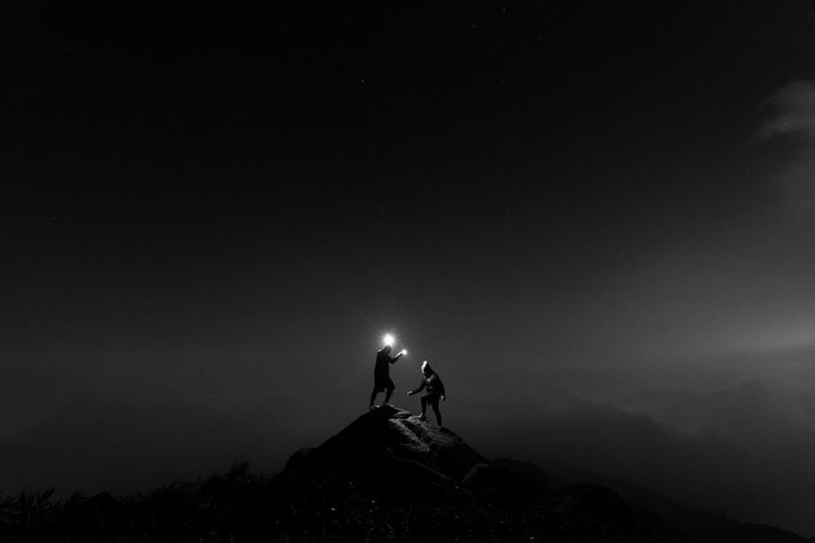 People Standing With Illuminated Lighting Equipment On Rock At Night