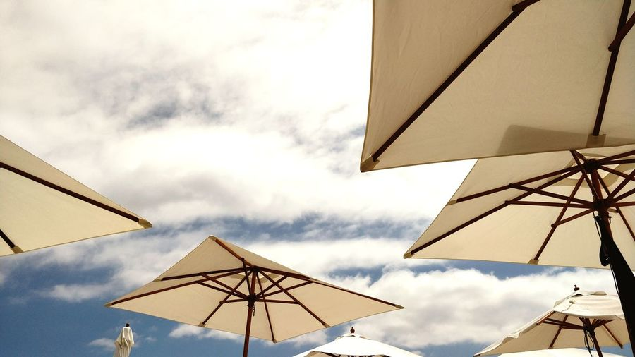 Low angle view of parasols against sky