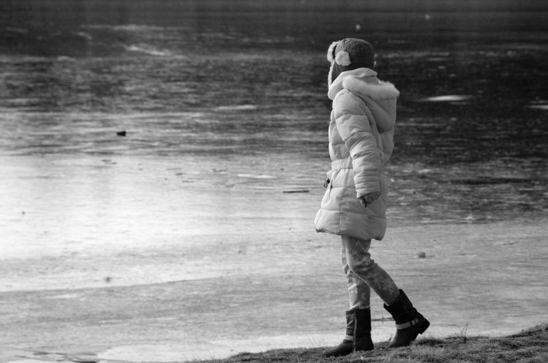 Side View Of Woman Wearing Warm Clothing While Walking At Lakeshore