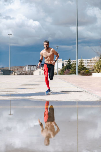 Shirtless Mature Man Jogging On Road Against Cloudy Sky