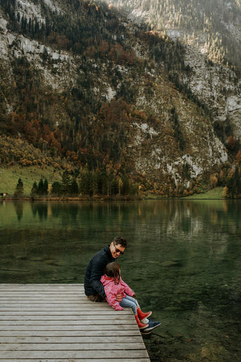 Side view of father and daughter sitting by lake