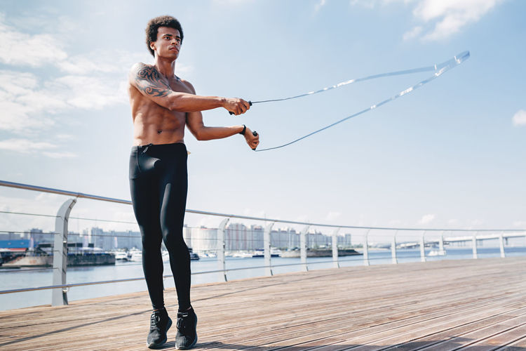 Shirtless young man jumping rope on promenade against sky