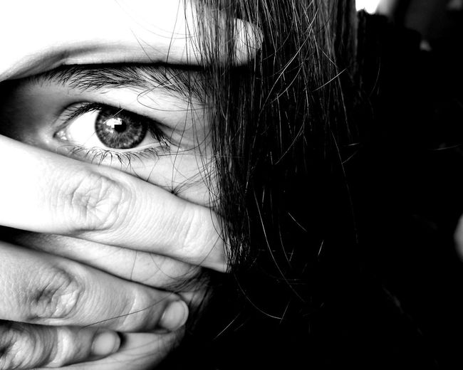 Close-Up Portrait Of Young Woman Covering Face With Hand