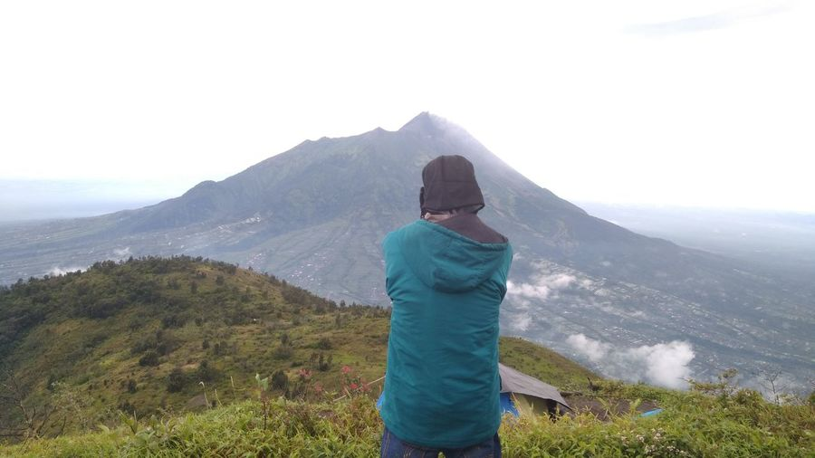 Rear view of man standing against mountain