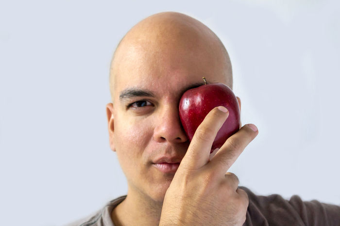 Studio Shot Human Body Part Shaved Head Looking At Camera Portrait Healthy Eating Human Face One Person Close-up Human Hand Adults Only People Adult One Man Only Young Adult White Background Human Eye Freshness Day Apple Red Apple Men Only Men Adult Fruit