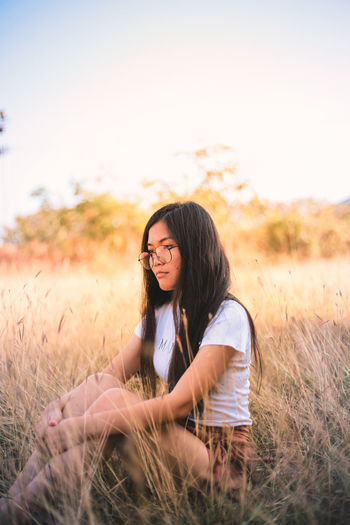 Side view of thoughtful young woman sitting on grassy field against sky