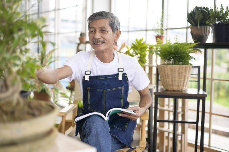 Senior man holding book sitting at greenhouse