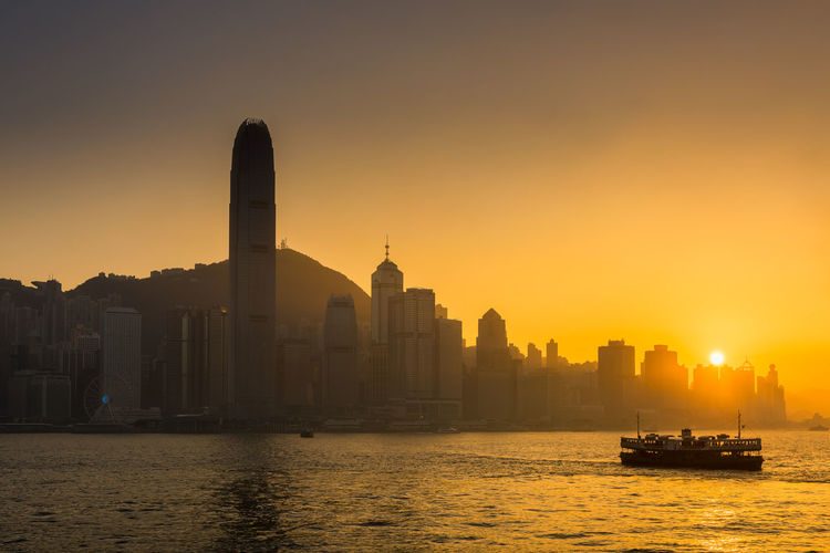 Hong Kong city at sunset scene Architecture Business City Cityscape Financial District  Harbor Hong Kong Hong Kong City Modern Modern Architecture Reflection Silhouette Skyscrapers Transportation Travel Victoria Building Downtown District Golden Hour Landscape Port Sunset Tall Urban Water